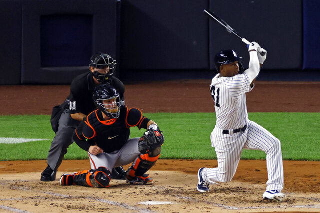 New York Yankees' Miguel Andujar follows through on a two-run double in front of Baltimore Orioles catcher Chance Sisco during the first inning of the second baseball game of a doubleheader, Friday, Sept. 11, 2020, in New York. (AP Photo/Adam Hunger)