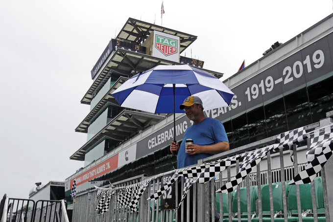 A fan waits as rain delays the final portion of qualifications for the Indianapolis 500 IndyCar auto race at Indianapolis Motor Speedway, Sunday, May 19, 2019, in Indianapolis. (AP Photo/Darron Cummings)