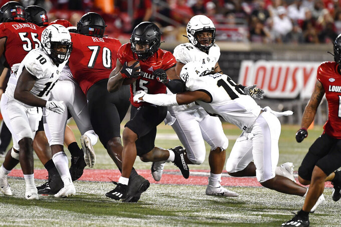 Central Florida defensive back Dyllon Lester (18) attempt to tackle Louisville running back Jalen Mitchell (15) during the second half of an NCAA college football game in Louisville, Ky., Friday, Sept. 17, 2021. AP Photo/Timothy D. Easley)