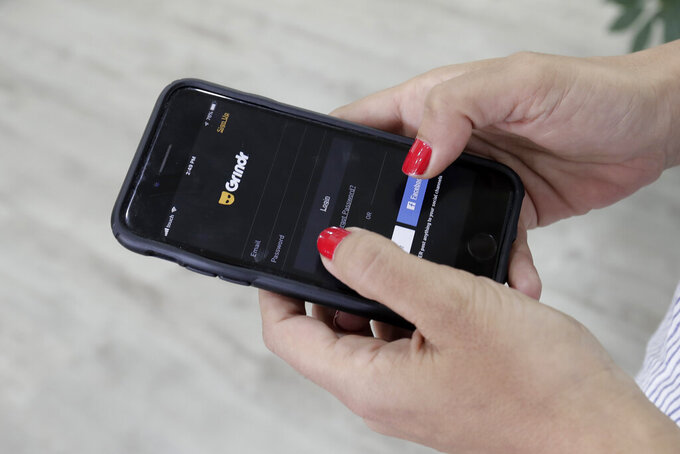 FILE - In this Wednesday, May 29, 2019 file photo, a woman looks at the Grindr app on her mobile phone in Beirut, Lebanon. With few rules in the U.S. guiding what companies can do with the vast amount of information they collect about what web pages people visit, the apps they use and where they carry their devices, there's little stopping similar spying activity targeting politicians, celebrities and just about anyone that's a target of another person's curiosity. (AP Photo/Hassan Ammar, File)