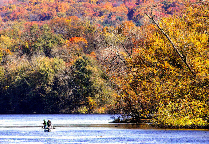 FILE - This Wednesday Oct. 22, 2008 file photo shows fall foliage as recreational anglers fish on the Connecticut River near Rocky Hill, Conn. Connecticut tourism officials plan to spend more money than usual promoting the state's fall foliage in an attempt help the industry rebound from the pandemic. (AP Photo/Bob Child, File)