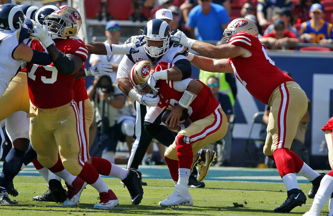 San Francisco 49ers quarterback Jimmy Garoppolo, bottom center, is sacked by -Los Angeles Rams defensive tackle Aaron Donald, top center, during the first half of an NFL football game Sunday, Oct. 13, 2019, in Los Angeles. (AP Photo/John Locher )