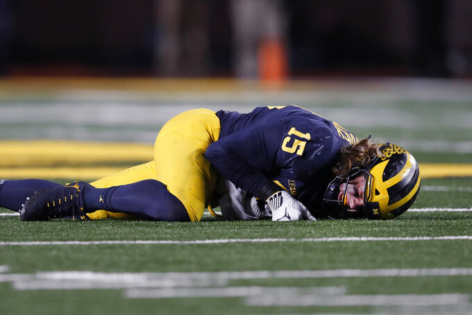 Michigan defensive lineman Chase Winovich winces on the ground before leaving the game with an injury in the second half of an NCAA college football game in Ann Arbor, Mich., Saturday, Nov. 17, 2018. (AP Photo/Paul Sancya)