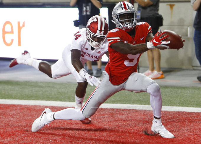 FILE - In this Oct. 6, 2018, file photo, Ohio State receiver Binjimen Victor, right, catches a touchdown in front of Indiana defensive back Andre Brown during the second half of an NCAA college football game in Columbus, Ohio. Victor, a junior, is coach Urban Meyer's pick for most improved Buckeye.  (AP Photo/Jay LaPrete, File)