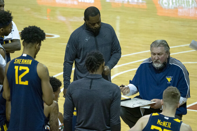 West Virginia head coach Bob Huggins draws a play for his team during the second half of an NCAA college basketball game against Texas, Saturday, Feb. 20, 2021, in Austin, Texas. (AP Photo/Michael Thomas)