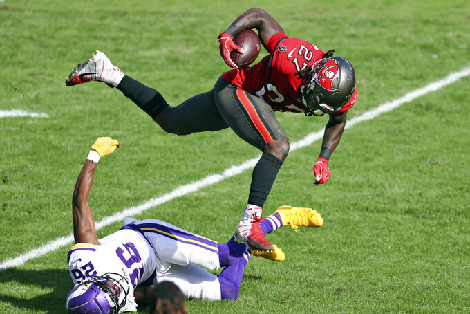 Tampa Bay Buccaneers running back Ronald Jones II (27) gets tripped up by Minnesota Vikings defensive back Chris Jones (26) during the first half of an NFL football game Sunday, Dec. 13, 2020, in Tampa, Fla. (AP Photo/Mark LoMoglio)