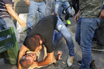 Protesters hold down a supporter of President Michel Aoun, after they found an automatic rifle used in a shooting in his car, in the town of Jal el-Dib, north of Beirut, Lebanon, Wednesday, Nov. 13, 2019. The man opened fire over the heads of protesters in a town north of Beirut Wednesday, the second shooting incident in as many days as tensions rise in Lebanon between supporters and opponents of President Michel Aoun amid nationwide protests. (AP Photo/Hassan Ammar)