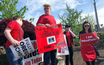 Teachers and others rally in Woodburn, Ore., joining thousands across Oregon who walked off the job Wednesday, May 8, 2019 to demand more money for schools, holding signs and wearing red shirts that have become synonymous with a nationwide movement pushing lawmakers to better fund education. Schools around the state, including Oregon's largest district, Portland Public Schools, planned to close for part of the day. (AP Photo/Sarah Zimmerman)