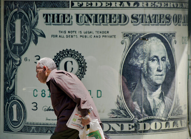 FILE - A man walks past a poster showing a US dollar outside an exchange office in Cairo, Egypt, in a Wednesday, Aug. 17, 2016 file photo.In 2019, before the coronavirus pandemic hit and the U.S. economy crashed, median household income was the highest ever on record, but the number of U.S. residents without health insurance also increased, the U.S. Census Bureau reported Tuesday, Sept. 15, 2020.  AP Photo/Amr Nabil, File)