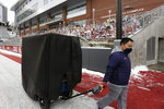 California operations employee Norman Mo removes equipment for his team from Martin Stadium after the NCAA college football game between Washington State and California was canceled due to COVID-19 positive testing and contact tracing on the California team, Saturday, Dec. 12, 2020, in Pullman, Wash. (AP Photo/Young Kwak)