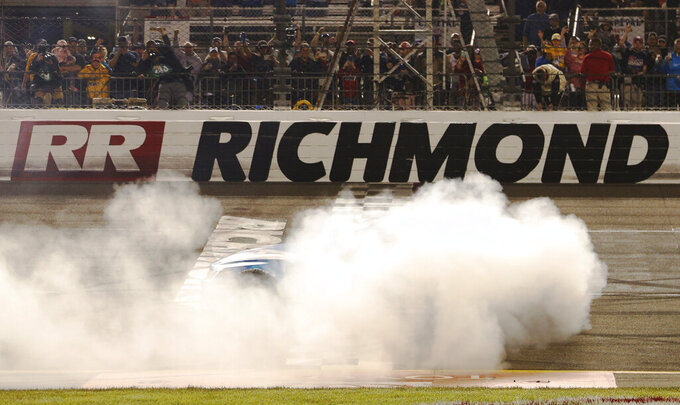 Martin Truex Jr. (19) does a burnout after winning the NASCAR Cup Series auto race at Richmond Raceway in Richmond, Va., Saturday, April 13, 2019. (AP Photo/Steve Helber)