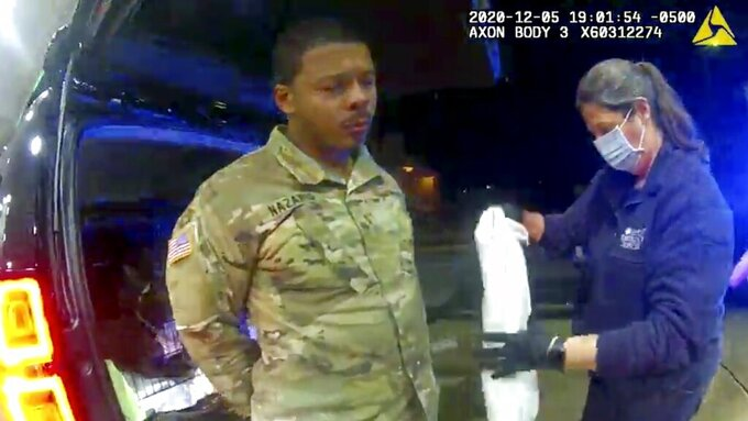 In this image made from Windsor, (Va.) Police video, Caron Nazario is helped by an EMT after he was sprayed with an agent by Windsor police after a traffic stop on Dec. 20, 2020, in Windsor, Va.  Nazario, a second lieutenant in the U.S. Army, is suing two Virginia police officers over a traffic stop during which he says the officers drew their guns and pointed them at him as he was dressed in uniform. Caron Nazario says his constitutional rights were violated by the traffic stop in the town of Windsor in December. (Windsor Police via AP)