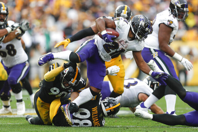 Baltimore Ravens running back Mark Ingram (21) leaps over Pittsburgh Steelers outside linebacker T.J. Watt (90) on a run in the second half of an NFL football game, Sunday, Oct. 6, 2019, in Pittsburgh. (AP Photo/Don Wright)