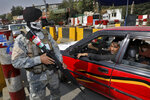 In this Wednesday, Sept. 25, 2019 photo, a masked Afghan policeman stands guard at a checkpoint ahead of presidential elections scheduled for Sept. 28, in Kabul, Afghanistan. Afghans facing down Taliban threats are torn between fear, frustration and sense of duty as they decide whether to go to the polls Saturday to choose a new president. (AP Photo/Ebrahim Noroozi)