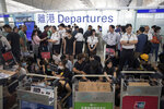 FILE - In this Aug. 13, 2019, file photo, airport security personnel stand guard as travelers walk past protesters holding a sit-in rally at the departure gate of the Hong Kong International Airport in Hong Kong. Visitor numbers to Hong Kong fell by nearly 40% in the second half of last year amid clashes between police and anti-government protesters. (AP Photo/Vincent Thian, File)