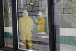 Men in hazardous material suits work inside the Abigail Hotel in San Francisco, Thursday, April 2, 2020. The hotel is one of several private hotels San Francisco has contracted with to take vulnerable people who show symptoms or are awaiting test results for the coronavirus. (AP Photo/Jeff Chiu)