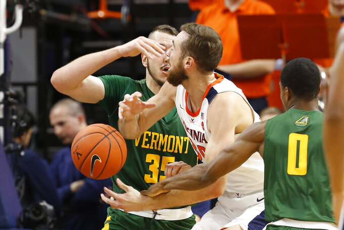 Virginia forward Jay Huff (30) looes the ball as Vermont forward Ryan Davis (35) and guard Stef Smith (0) defend during the first half of an NCAA college basketball game Tuesday, Nov. 19, 2019, in Charlottesville, Va. (AP Photo/Steve Helber)