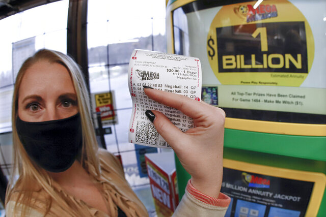 A patron, who did not want to give her name, shows the ticket she had just purchased for the Mega Millions lottery drawing at the lottery ticket vending kiosk in a Smoker Friendly store, Friday, Jan. 22, 2021, in Cranberry Township, Pa. The jackpot for the Mega Millions lottery game has grown to $1 billion ahead of Friday night's drawing after more than four months without a winner. (AP Photo/Keith Srakocic)