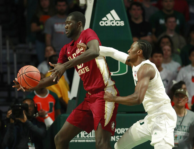 Florida State center Christ Koumadje, left, and Miami center Ebuka Izundu battle for the ball during the first half of an NCAA college basketball game, Sunday, Jan. 27, 2019, in Coral Gables, Fla. (AP Photo/Wilfredo Lee)