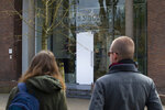 Two people look at the glass door which was smashed during a break-in at the Singer Museum in Laren, Netherlands, Monday March 30, 2020. Police are investigating a break-in at a Dutch art museum that is currently closed because of restrictions aimed at slowing the spread of the coronavirus, the museum and police said Monday. (AP Photo/Peter Dejong)
