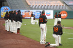 San Francisco Giants manager Gabe Kapler, right, kneels during the national anthem before a baseball game between the Giants and the San Diego Padres in San Francisco, Saturday, Sept. 26, 2020. (AP Photo/Eric Risberg)