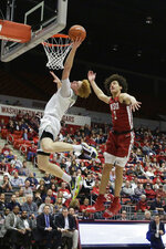 Arizona guard Nico Mannion, left, shoots in front of Washington State forward CJ Elleby during the second half of an NCAA college basketball game in Pullman, Wash., Saturday, Feb. 1, 2020. Arizona won 66-49. (AP Photo/Young Kwak)