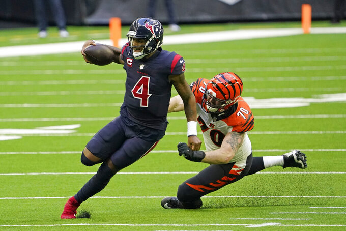 Houston Texans quarterback Deshaun Watson (4) runs for a first down as Cincinnati Bengals defensive end Margus Hunt (70) reaches to tackle him during the second half of an NFL football game Sunday, Dec. 27, 2020, in Houston. (AP Photo/Sam Craft)