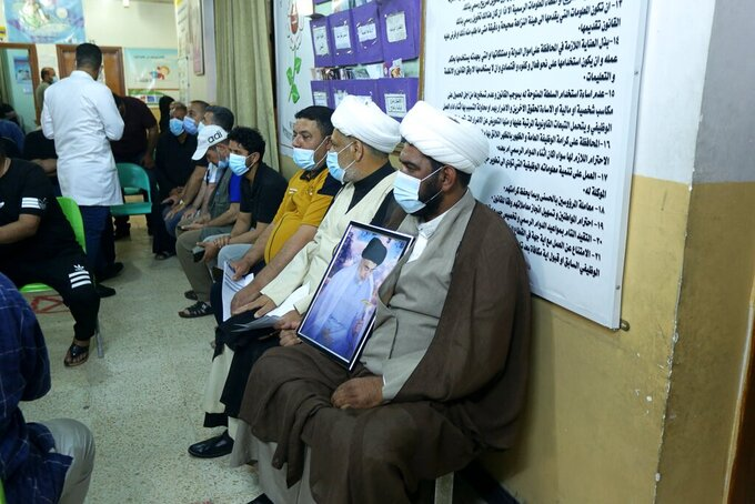 A follower of populist Shiite cleric Muqtada al-Sadr holds a picture of him while waiting with others to receive a dose of the Chinese Sinopharm coronavirus vaccine at a clinic in Sadr City, Baghdad, Iraq, Wednesday, May 4, 2021. Iraq's vaccine rollout had been faltering for weeks. Apathy, fear and rumors kept many from getting vaccinated despite a serious surge in coronavirus infections and calls by the government for people to register for shots. It took al-Sadr's public endorsement of vaccinations — and images of him getting the shot — to turn things around. (AP Photo/Hadi Mizban)