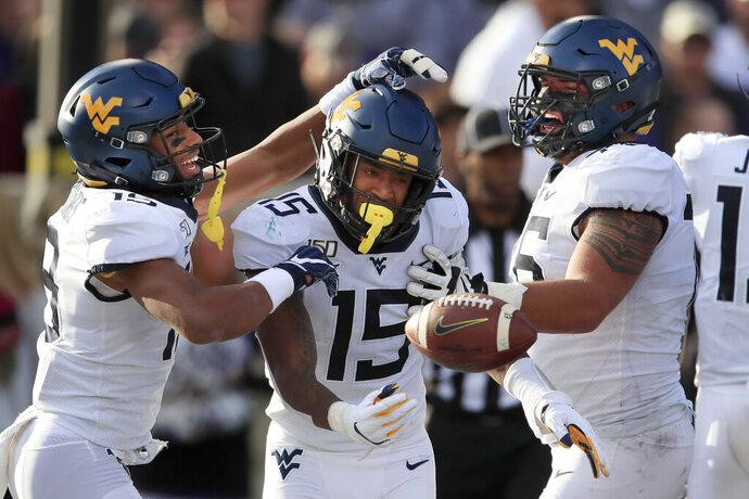 West Virginia wide receiver George Campbell (15) is congratulated by teammates Ali Jennings (19) and Chase Behrndt, right, after his touchdown in the first half of an NCAA college football game against Kansas State in Manhattan, Kan., Saturday, Nov. 16, 2019. (AP Photo/Orlin Wagner)