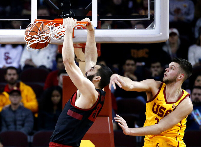 Stanford's Josh Sharma, left, dunks while defended by Southern California's Nick Rakocevic during the first half of an NCAA college basketball game Sunday, Jan. 6, 2019, in Los Angeles. (AP Photo/Ringo H.W. Chiu)