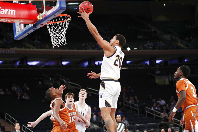 California guard Matt Bradley (20) goes up for a layup as Texas guard Matt Coleman III , far left, Texas center Will Baker (50) and California forward Lars Thiemann (21) watch from the floor during the first half of an NCAA college basketball game in the 2K Empire Classic, Friday, Nov. 22, 2019, in New York. Texas guard Courtney Ramey (3) is at far right.(AP Photo/Kathy Willens)