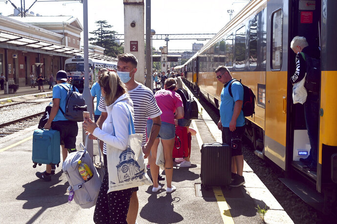 Passengers disembark from a train that arrived from the Czech Republic in Rijeka, Croatia, Wednesday, July 1, 2020. A train carrying some 500 tourists from the Czech Republic has arrived to Croatia as the country seeks to attract visitors after easing lockdown measures against the new coronavirus. (AP Photo)