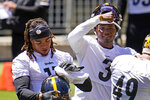 Pittsburgh Steelers quarterback Dwayne Haskins, center, and wide receiver Chase Claypool, left, take a break during the team's NFL mini-camp football practice in Pittsburgh, Wednesday, June 16, 2021. (AP Photo/Gene J. Puskar)