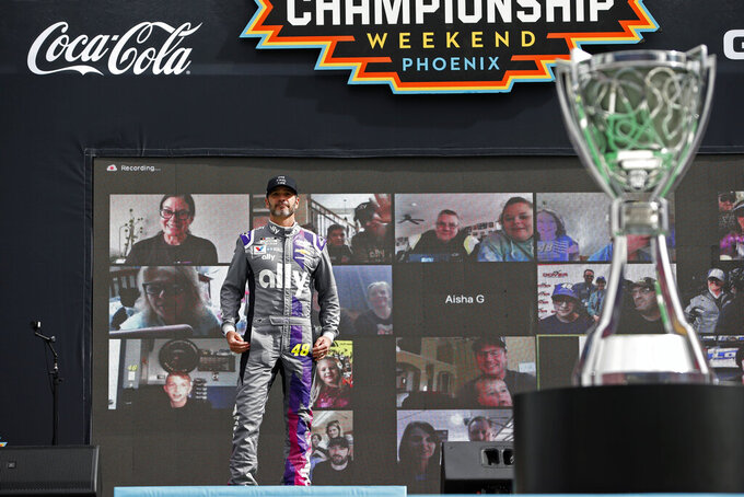 Jimmie Johnson stands on stage during driver introductions prior to the NASCAR Cup Series auto race at Phoenix Raceway, Sunday, Nov. 8, 2020, in Avondale, Ariz. (AP Photo/Ralph Freso)