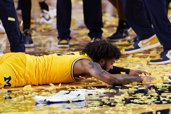 Michigan forward Isaiah Livers makes confetti angels on the court after the team's win over Michigan State in an NCAA college basketball game, Thursday, March 4, 2021, in Ann Arbor, Mich. Michigan won the Big Ten title. (AP Photo/Carlos Osorio)