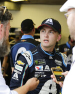 William Byron, center, talks with reporters in his garage after he wrecked his car during a NASCAR auto race practice at Daytona International Speedway, Thursday, July 4, 2019, in Daytona Beach, Fla. (AP Photo/Terry Renna)
