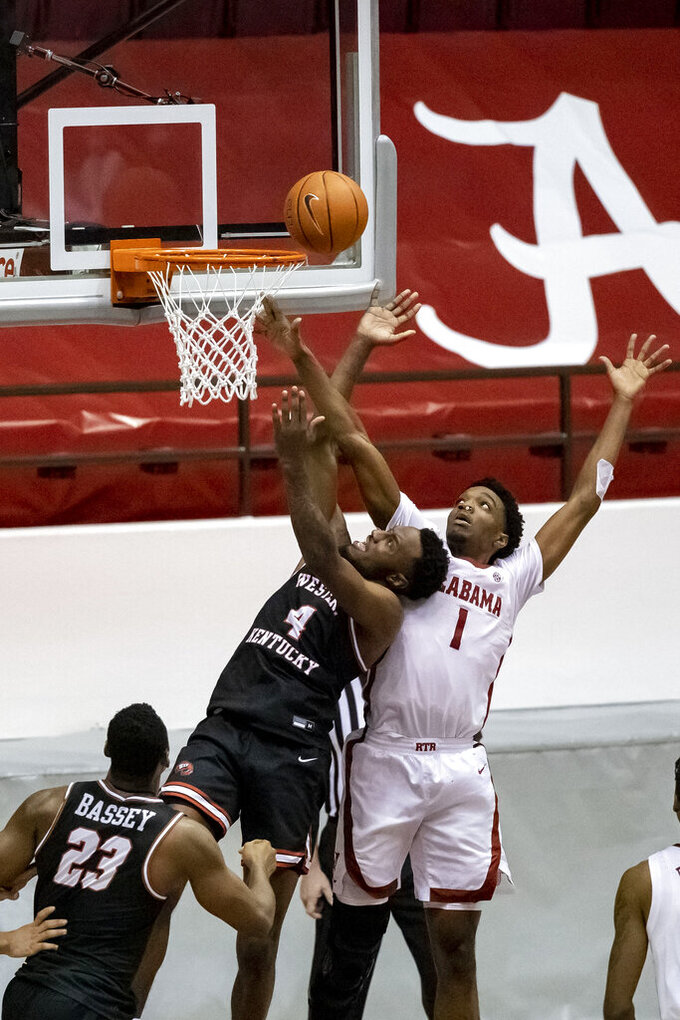 Alabama forward/guard Herbert Jones (1) is called for a goal-tend as Western Kentucky guard Josh Anderson (4) shoots during the second half of an NCAA college basketball game, Saturday, Dec. 19, 2020, in Tuscaloosa, Ala. The goal tend with only seconds to play gave Western Kentucky the final margin of 73-71.(AP Photo/Vasha Hunt)