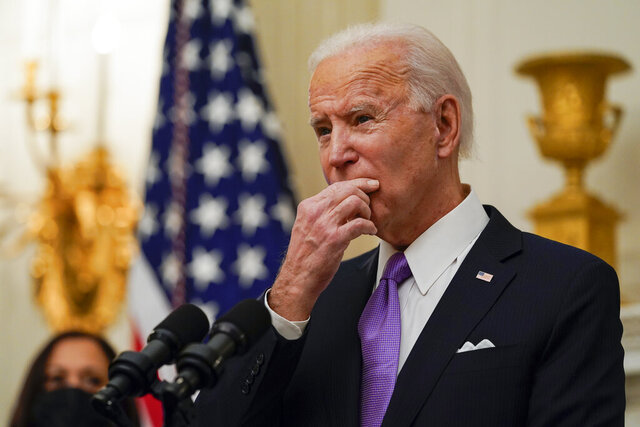 President Joe Biden pauses as he speaks about the coronavirus, accompanied by Vice President Kamala Harris, in the State Dinning Room of the White House, Thursday, Jan. 21, 2021, in Washington. (AP Photo/Alex Brandon)