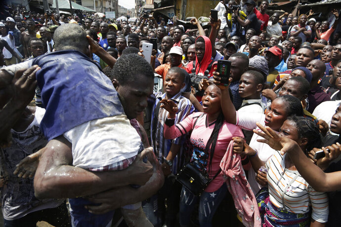 A child is rescued from the rubble of a collapsed building in Lagos, Nigeria, Wednesday, March 13, 2019. Rescue efforts are underway in Nigeria after a three-story school building collapsed while classes were in session, with scores of school children thought to be inside at the time. (AP Photo/Sunday Alamba)
