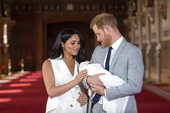 FILE - In this Wednesday May 8, 2019 file photo Britain's Prince Harry and Meghan, Duchess of Sussex, pose during a photocall with their newborn son Archie, in St George's Hall at Windsor Castle, Windsor, south England. The second baby for the Duke and Duchess of Sussex is officially here: Meghan gave birth to a healthy girl on Friday, June 4, 2021. (Dominic Lipinski/Pool via AP, file)