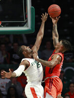Virginia Tech guard Ahmed Hill, right, goes up for a shot against Miami center Ebuka Izundu (15) during the first half of an NCAA college basketball game Wednesday, Jan. 30, 2019, in Coral Gables, Fla. (AP Photo/Wilfredo Lee)