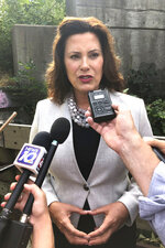 Gov. Gretchen Whitmer speaks with reporters after inspecting the Elm Street bridge over the Red Cedar River, Monday, Aug. 12, 2019, in Lansing, Mich. Whitmer says it is important that the public knows the seriousness of the state's