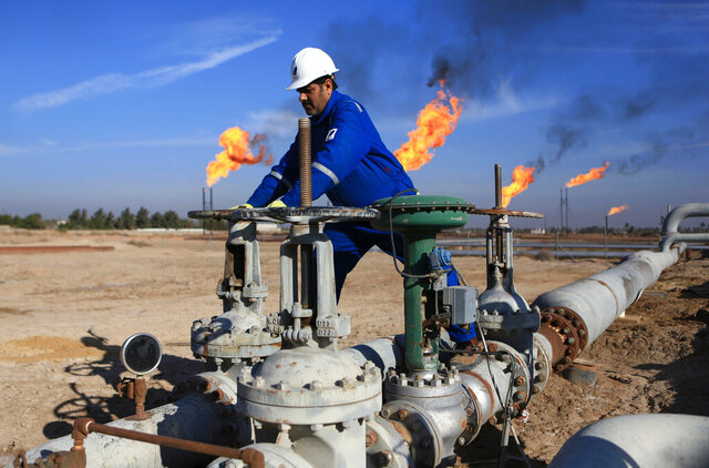FILE - In this Jan. 12, 2017 file photo, a worker operates valves in Nihran Bin Omar field north of Basra, Iraq. The U.S. has signaled to Iraq it's willingness to extend sanctions waivers enabling the country to continue importing vital Iranian gas and electricity imports, three Iraqi officials said this week. The decision comes amid strained U.S.-Iraqi ties following last month's Washington-directed airstrike that killed a high-profile Iranian general on Iraqi soil. (AP Photo/Nabil al-Jurani, File)