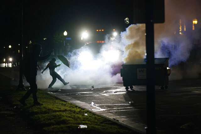 A protester kicks a smoke canister Tuesday, Aug. 25, 2020 in Kenosha, Wis. Anger over the Sunday shooting of Jacob Blake, a Black man, by police spilled into the streets for a third night. (AP Photo/Morry Gash)