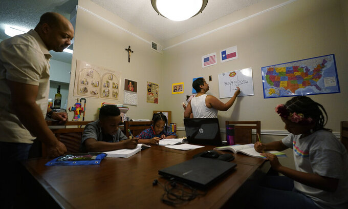 """Arlena Brown, center, holds her youngest child, Lucy, 9 months, as she and husband, Robert, left, lead their other children, from left, Jacoby, 11; Felicity, 9, and Riley, 10, through math practice at their home in Austin, Texas, Tuesday, July 13, 2021. """"I didn't want my kids to become a statistic and not meet their full potential,"""" said Robert, a former teacher who now does consulting. """"And we wanted them to have very solid understanding of their faith."""" (AP Photo/Eric Gay)"""