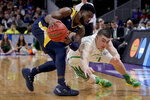 Oregon guard Payton Pritchard, right, dives past UC Irvine guard Max Hazzard during the first half of a second-round game in the NCAA men's college basketball tournament Sunday, March 24, 2019, in San Jose, Calif. (AP Photo/Jeff Chiu)