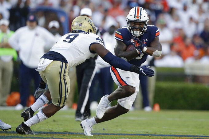 Auburn running back Tank Bigsby (4) carries the ball as he tries to get around Akron linebacker Jeslord Boateng (9) during the first half of an NCAA college football game Saturday, Sept. 4, 2021, in Auburn, Ala. (AP Photo/Butch Dill)