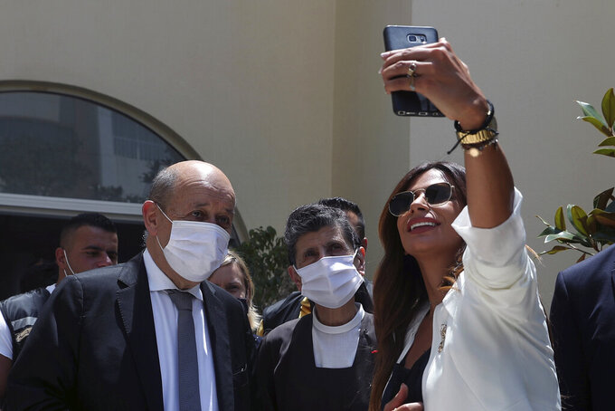 A Lebanese woman takes a selfie with French Foreign Minister Jean-Yves Le Drian, during his visit to the Carmel Saint Joseph school in Mechref district, south of the capital Beirut, Lebanon, Friday, July 24, 2020.  Le Drian pledged on Friday €15 million ($17 million) in aid to Lebanon's schools, struggling under the weight of the country's major economic crisis. (AP Photo/Bilal Hussein)