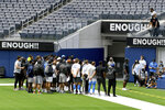 Los Angeles Chargers head coach Anthony Lynn, with players behind him, talks to the media about the cancelation of practice and a scrimmage at SoFi Stadium in Inglewood, Calif., Thursday, Aug. 27, 2020. The team canceled practice due to the recent shooting of Jacob Blake. Lynn canceled practice after his players held a wide-ranging conversation in the locker room spurred by the shooting of Blake, a Black man, in Wisconsin last weekend. (Hans Gutknecht/The Orange County Register via AP)