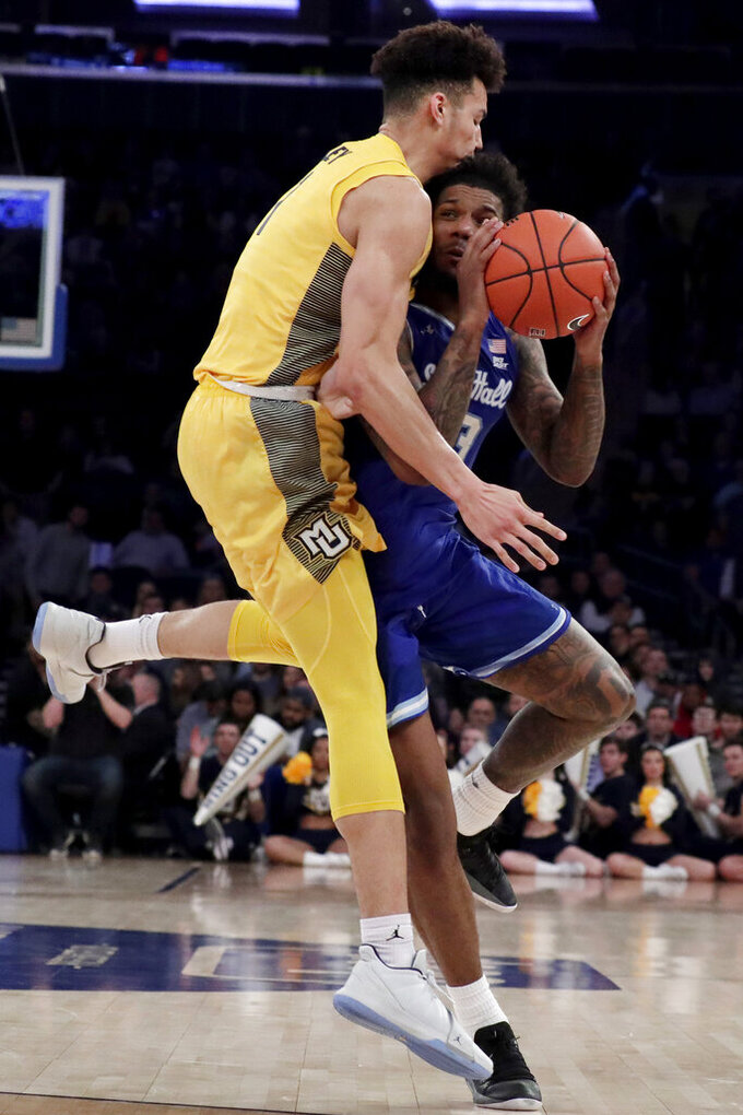 Seton Hall guard Myles Powell, right, is fouled by Marquette forward Brendan Bailey during the second half of an NCAA college basketball semifinal game in the Big East men's tournament, Friday, March 15, 2019, in New York. Seton Hall won 81-79. (AP Photo/Julio Cortez)